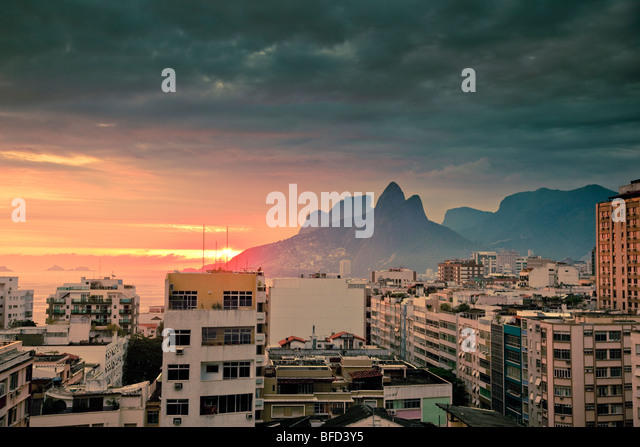 view over tops of residential buildings and mountains at sunset in Ipanema Rio de Janeiro Brazil - Stock Image