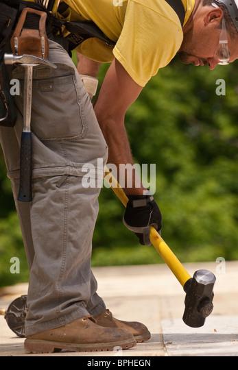 Carpenter using a sledgehammer - Stock Image