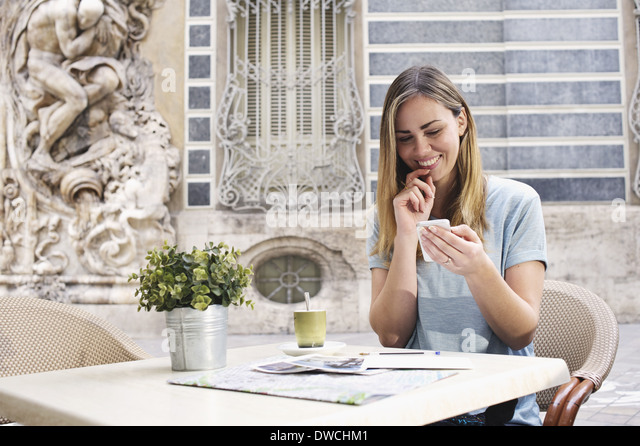 Young woman looking at cellphone outside Museum of Ceramics, Valencia, Spain - Stock Image