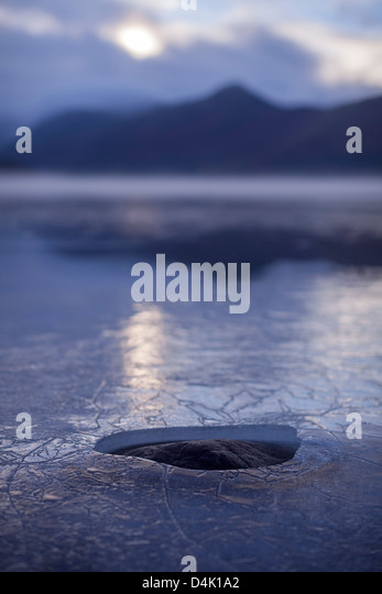 Hole in layer of ice on rural lake - Stock Image