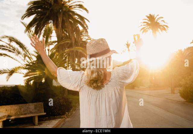 Happy mature blond woman holiday drinking cocktail - Stock-Bilder