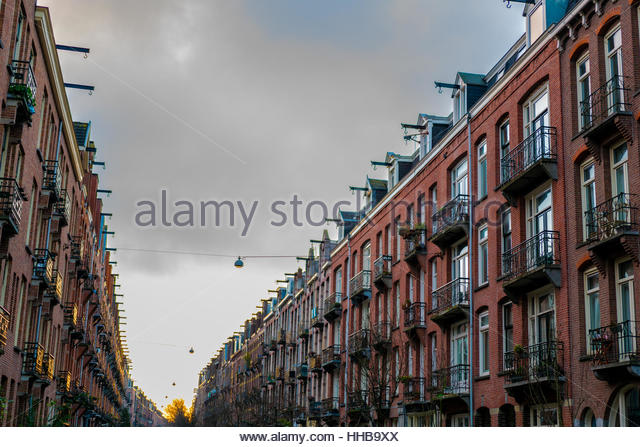 Street with typical amsterdam houses on both sides in winter - Stock Image