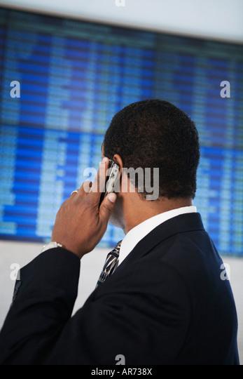 African businessman looking at Arrival Departure board - Stock-Bilder