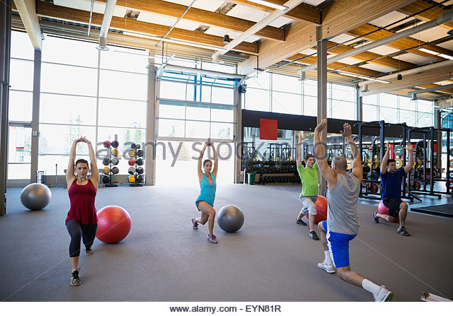 Exercise class doing lunges with arms raised gym - Stock Image