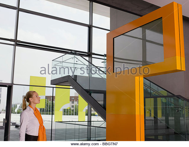 Businesswoman looking at information monitor - Stock Image