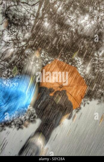 Reflection of a man walking in the rain with an orange umbrella. - Stock Image