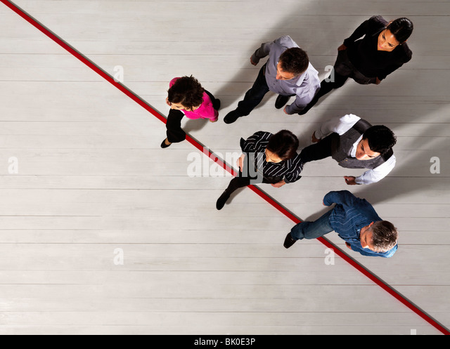 Business people crossing a red line - Stock Image