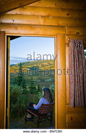 Guest relaxes outside her cabin & enjoys the view at Camp Denali Lodge, Denali National Park, Alaska - Stock Image