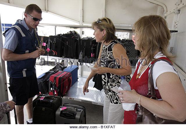 Arkansas Bentonville Northwest Arkansas Regional Airport XNA plane side luggage check man employee suitcase woman - Stock Image