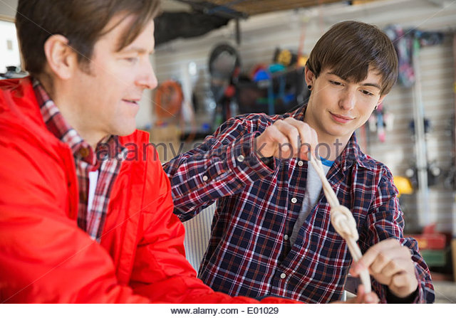 Father teaching son to tie knots in garage - Stock Image