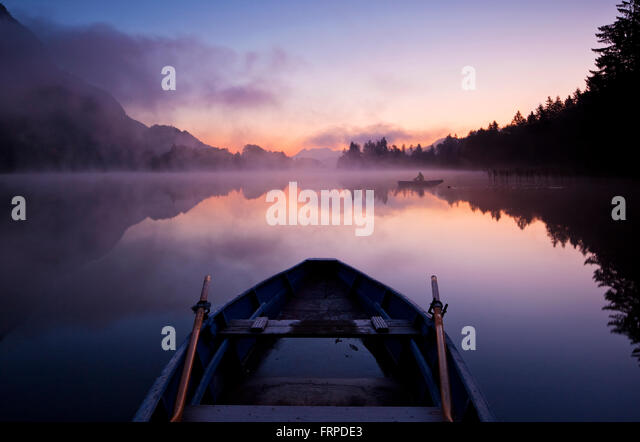 Rowing boat at dawn, Lake Reintal, Kramsach, Tyrol, Austria - Stock Image