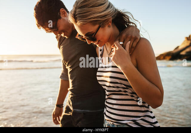 Portrait of happy young couple walking on sea shore. Man and woman on beach holiday. - Stock Image