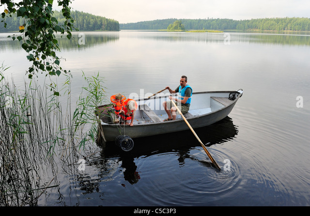 Side view of a man with two kids in life jackets oaring a boat in the peaceful lake - Stock Image