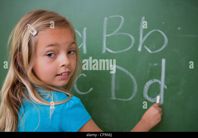 Cute schoolgirl writing letters - Stock Image