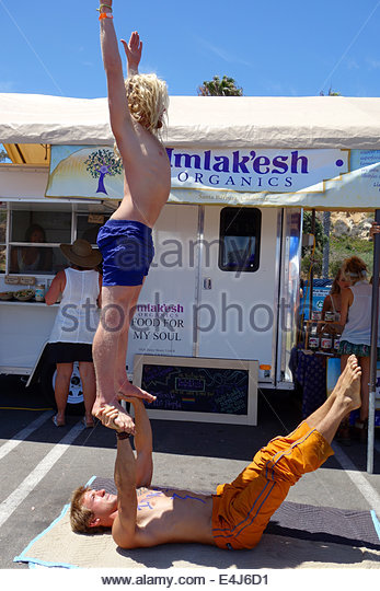 Acrobats perform to draw attention to their organic food truck. - Stock Image