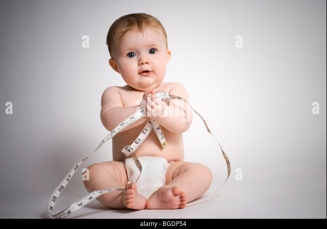Baby girl with tape measure - Stock Image