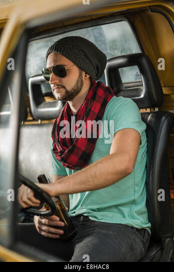 Young man with bottle of beer sitting in pick-up truck - Stock Image