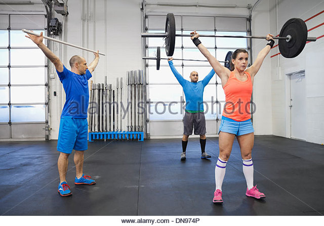 Gym instructor training participants on clean and jerk technique - Stock Image