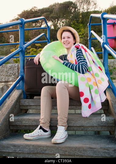 Teenage girl with suitcase on steps - Stock Image