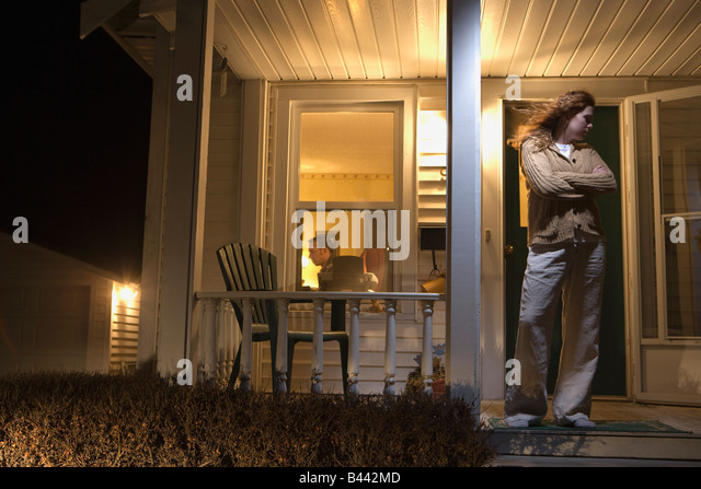 Woman standing outside of her house - Stock Image