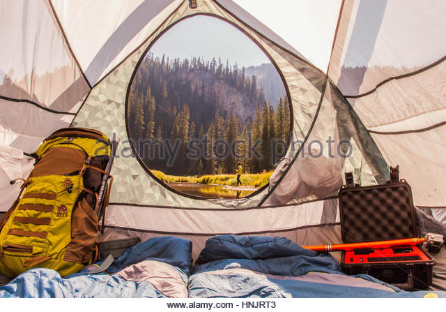 A view from inside the tent at a man fly fishing. - Stock-Bilder