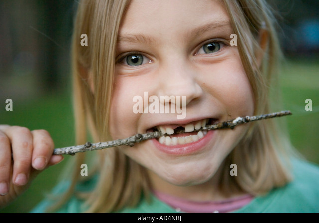 A young girl with a missing front tooth biting a stick - Stock-Bilder
