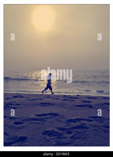 Young boy running along a beach on a hazy summer morning - Stock-Bilder