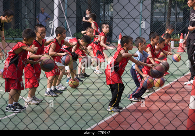 Children playing basketball at school, Guangzhou, Guangdong, China - Stock Image