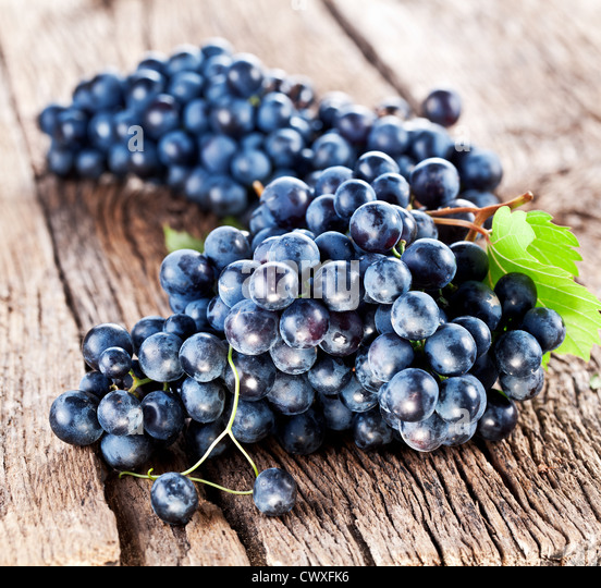 Grapes on a old wooden table. - Stock Image