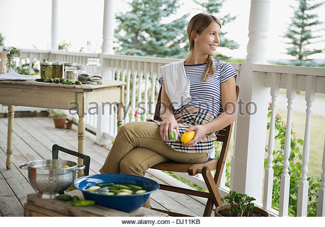 Young woman washing vegetables on porch - Stock-Bilder