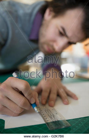 Close up of designer using ruler and bradawl on cutting mat - Stock Image
