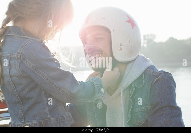 Young girl helping her father put on crash helmet - Stock Image
