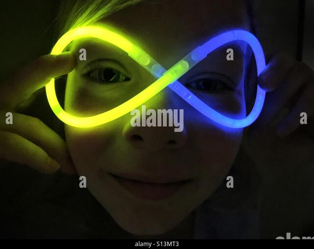 A girl plays with glow sticks, twisting them into the shape of goggles in front of her face. - Stock Image