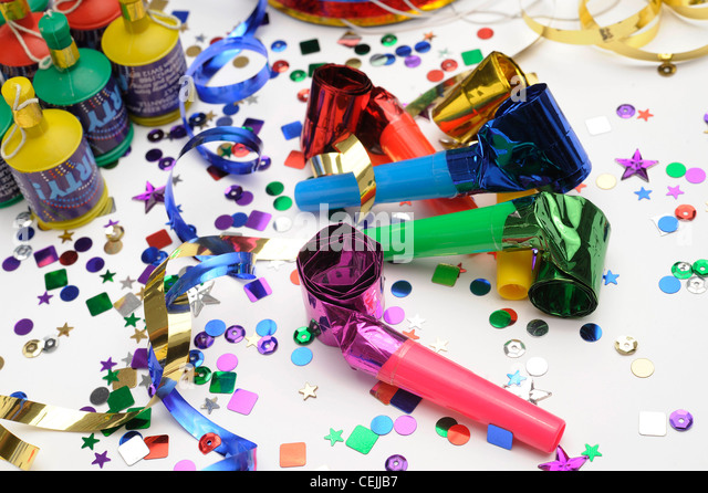 A still life image of colourful confetti, horn blowers, streamers and party poppers on white background - Stock Image