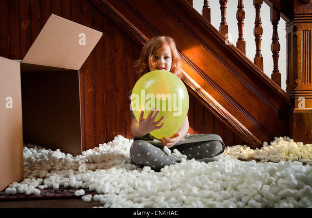 Girl playing with balloon and packing material from cardboard box - Stock Image