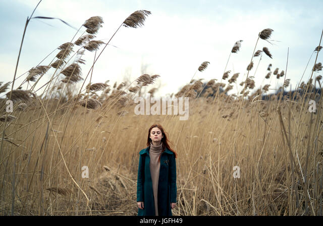 Caucasian woman standing in field with eyes closed - Stock Image