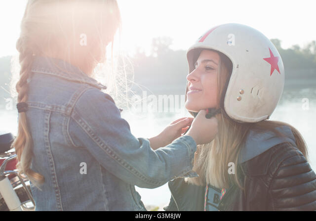 Young girl helping her mother put on crash helmet - Stock Image