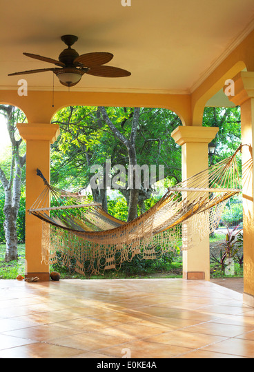 An inviting hammock hangs on a sunny porch with the tropics in the background. - Stock Image