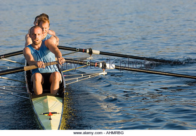 Male athletes rowing in canal - Stock Image