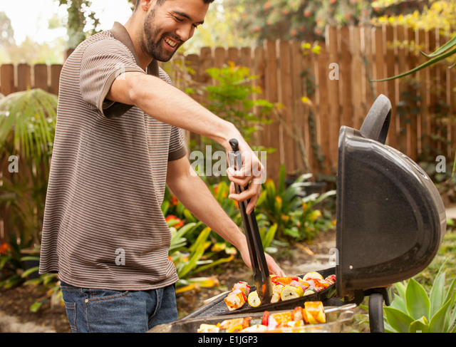 Man cooking vegetable skewers on barbecue - Stock Image