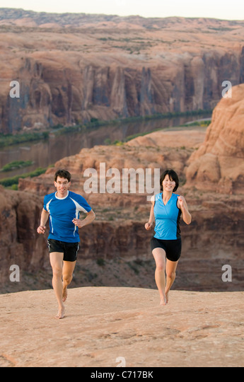 Man and woman barefoot running on sandstone above the Colorado River, Moab, Utah. - Stock Image
