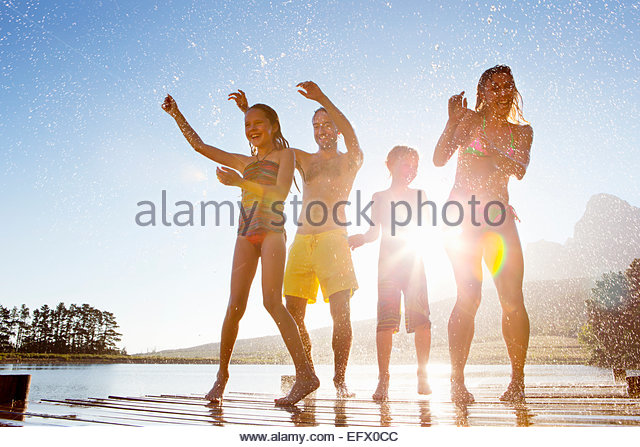 Happy family having water fight on jetty - Stock-Bilder
