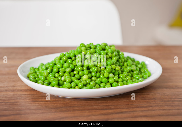 Close up of plate of peas on table - Stock Image
