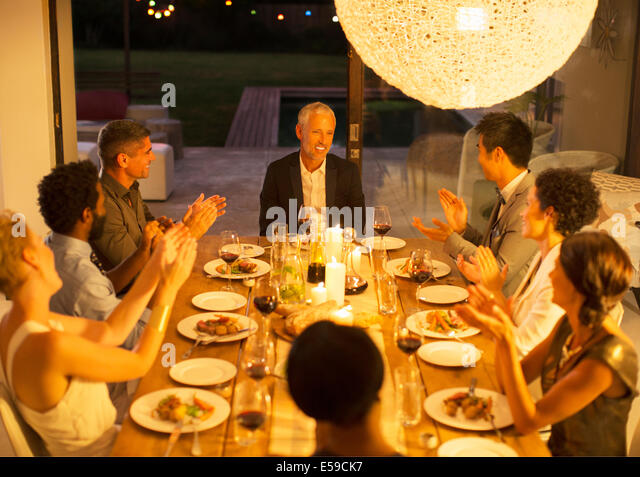 Friends applauding man at dinner party - Stock Image