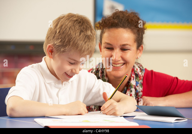 Schoolboy Studying In Classroom With Teacher - Stock Image