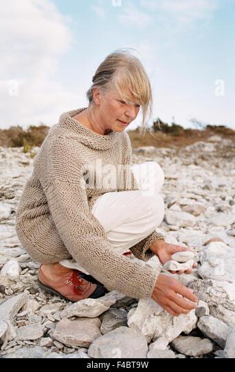 autumn beach color image Gotland grey-haired mature adult nature outdoors Scandinavia sitting stone summer Sweden - Stock-Bilder
