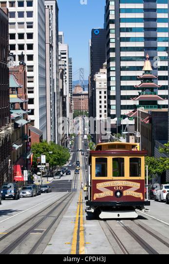 Cable car crossing California Street with Bay Bridge backdrop in San Francisco, California, USA - Stock Image