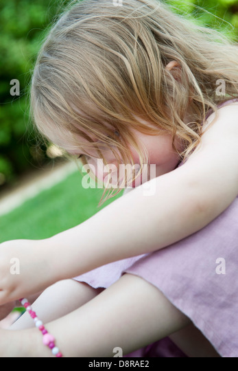 Little girl sitting outdoors, playing with beaded necklace - Stock Image