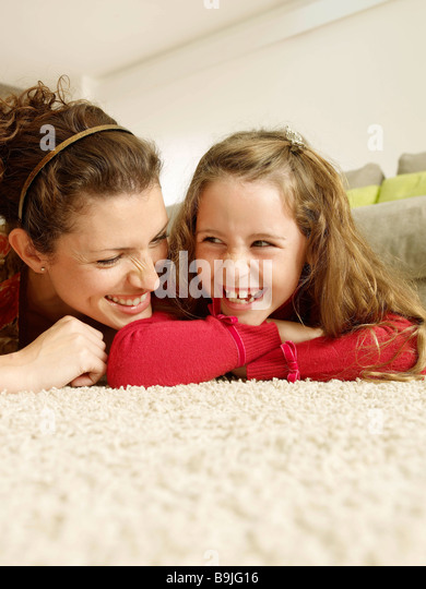 Mother and daughter lying on rug - Stock Image