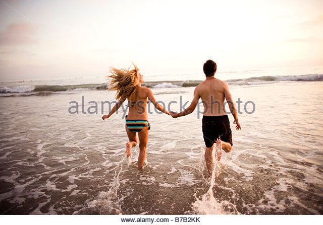 Couple holding hands and running through surf - Stock Image